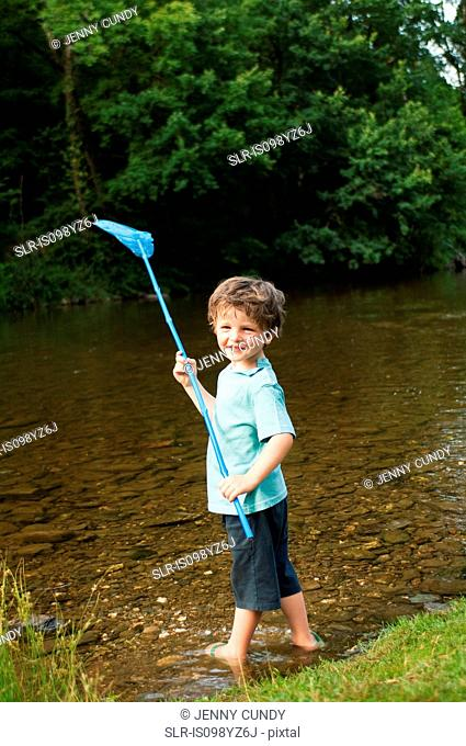 Boy holding fishing net by river