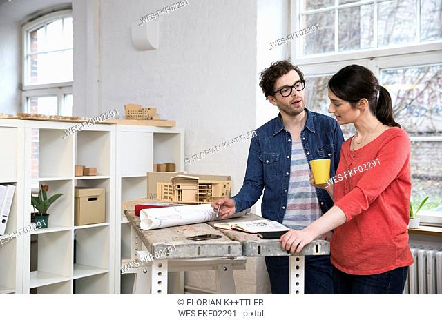 Man and woman discussing draft in office