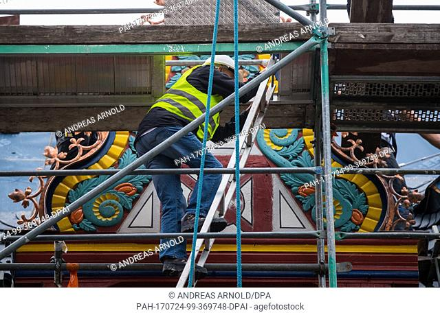 A man climbs down a scaffold outside of the Golden Scale in Frankfurt am Main, Germany, 24 July 2017. The reparations are part of a large scale city...