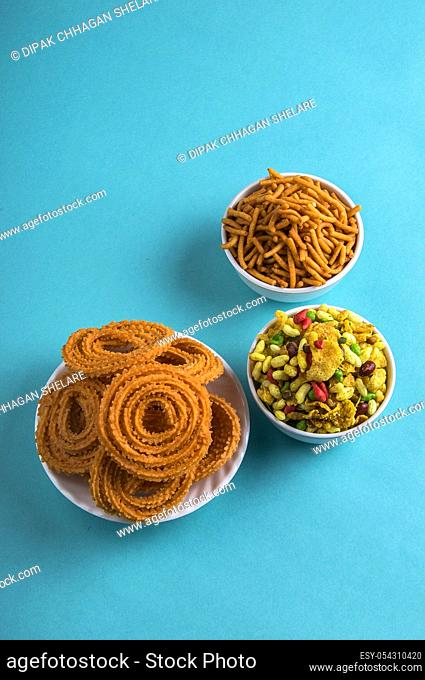 Indian Snack : Chakli, chakali or Murukku and Besan (Gram flour) Sev and chivada or chiwada on blue background. Diwali Food