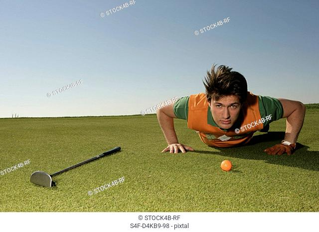 Young man on golf course preparing to putt