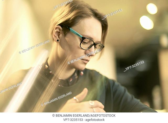 woman indoors, wearing spectacles, in Munich, Germany