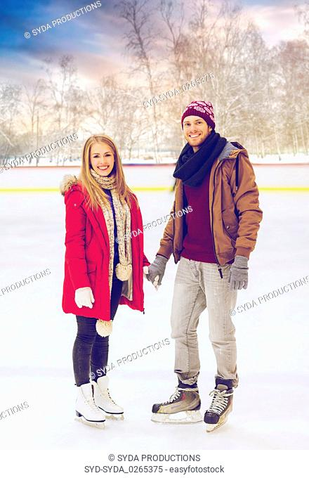 happy couple holding hands on outdoor skating rink