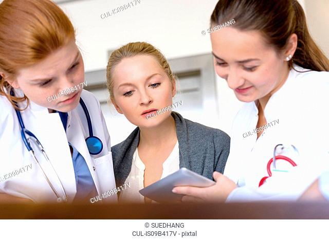 Female doctors looking at digital tablet in hospital
