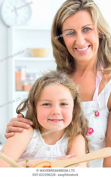 Smiling mother hugging daughter while looking directly into the camera and makin