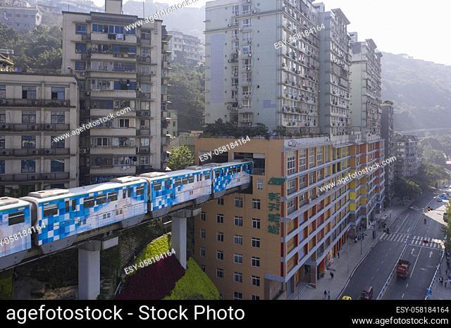 Aerial view of subway train at Liziba station in Chongqing, China, passing through building