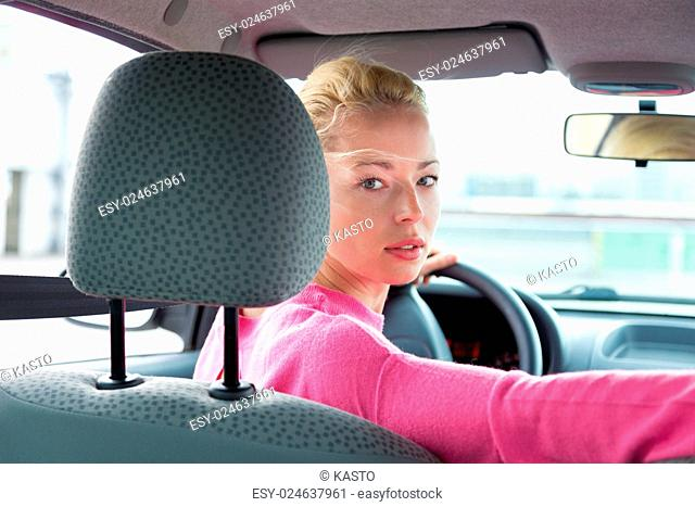 Beautiful young lady looking back through the rear window from the front seat of a car while reversing