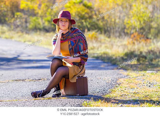 Young woman dressed old-fashioned is waiting for transport