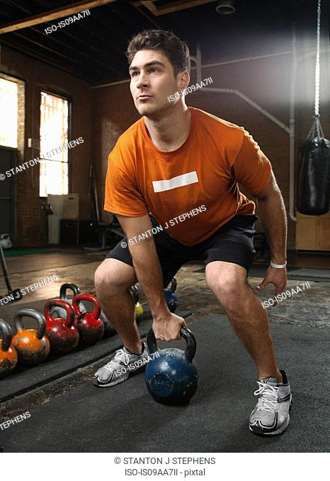 Bodybuilder lifting kettlebells in gym