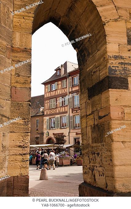 Place de la Cathedrale, Colmar, Alsace, France, Europe  View through stone arch in city square