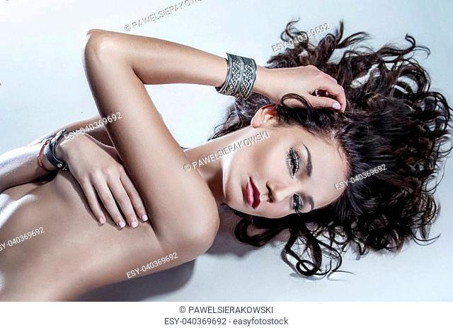 Portrait of beautiful brunette posing, lying on the floor