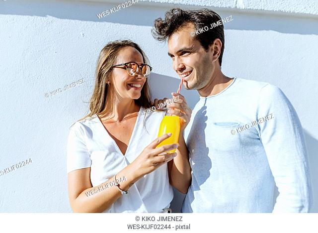 Happy couple sharing an orange juice on a sunny day