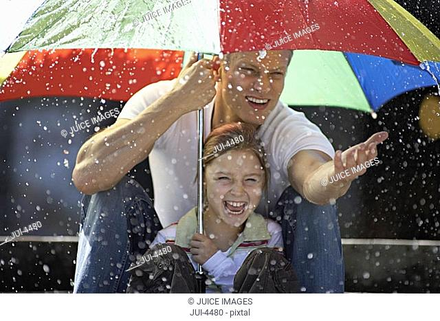 Father and daughter 9-11 sitting on steps in rain beneath large umbrella, smiling, portrait