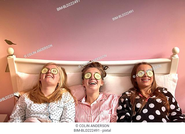Caucasian girls wearing cucumber slices on eyes in bed