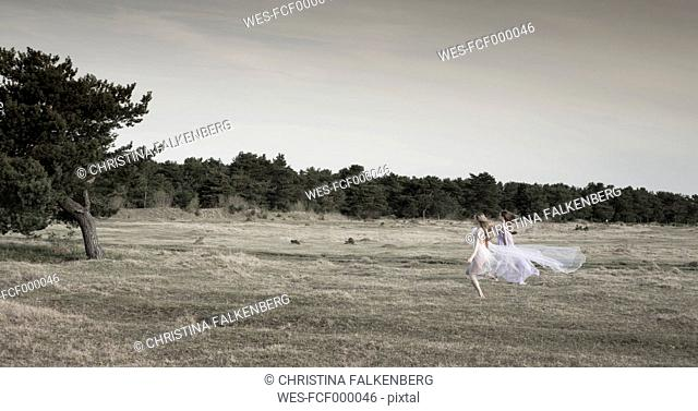 Germany, Bavaria, Froettmaning Heath, young women wearing a tulle dress and running