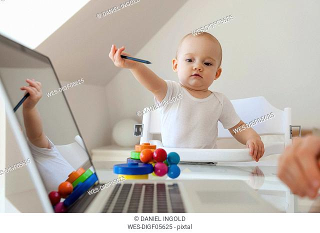 Little daughter playing and mother using laptop at table at home