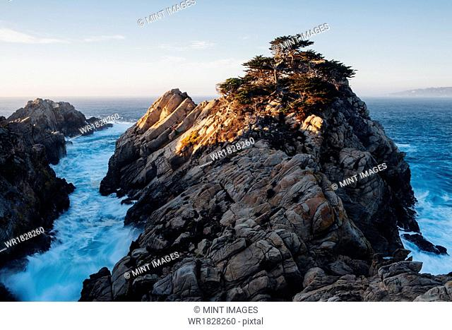 Dramatic cliffs and coastline at dusk in the Point Lobos State Reserve on the Pacific coastline. White foaming water