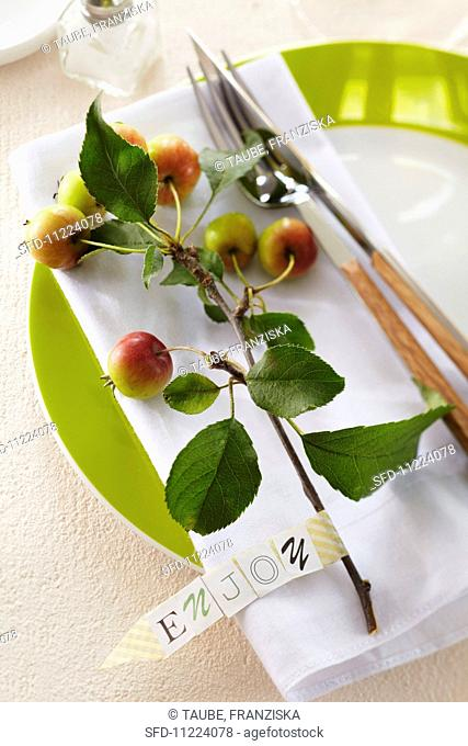 A sprig of ornamental apples on a plate with a label saying 'Enjoy' as a table decoration