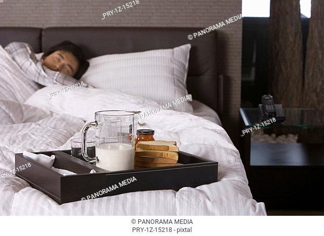 Man sleeping in bed, breakfast setting aside