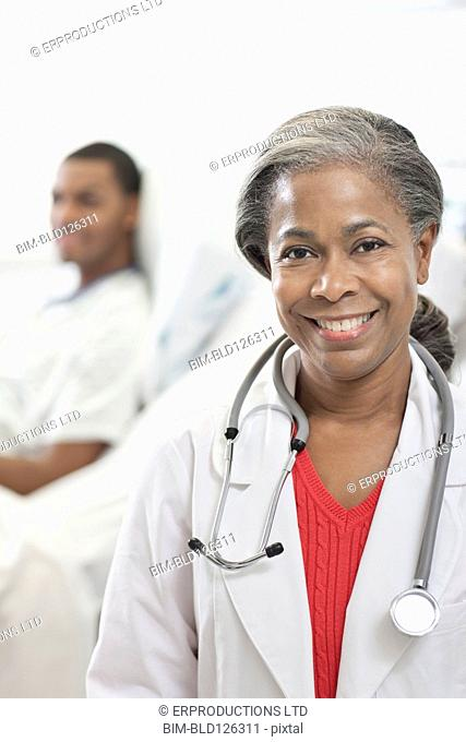 Doctor smiling in hospital with patient in background