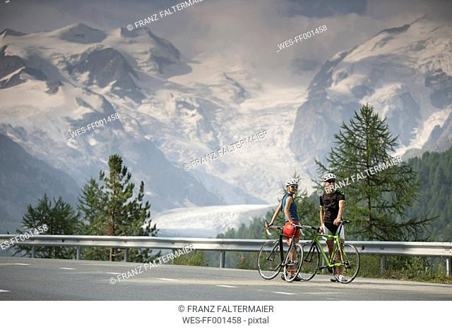 Switzerland, Engadin, two cyclists on Bernina Pass road in front of Morteratsch Glacier