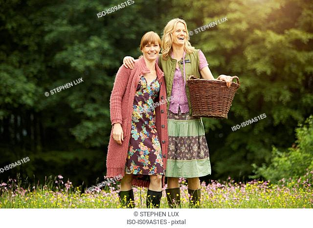 Portrait of two women in meadow with basket