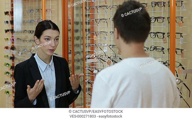 Optometrist helping client to choose eyeglasses