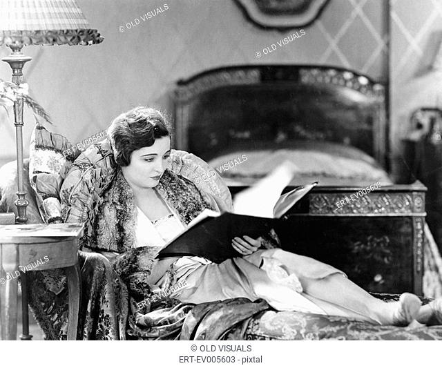 Young woman reclining in an armchair and reading a book in her bed room All persons depicted are not longer living and no estate exists Supplier warranties that...
