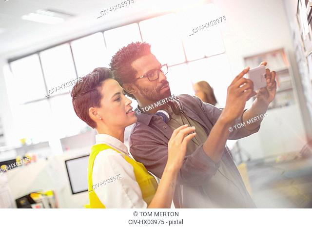 Focused creative business people using camera phone in office