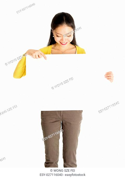 Portrait of casual Asian girl hand holding blank white paper card and pointing on it, isolated on white background