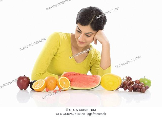 Woman looking at a row of assorted fresh fruits