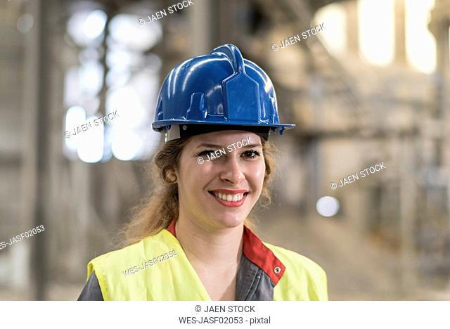 Portrait of smiling female worker wearing hard hat standing in a factory