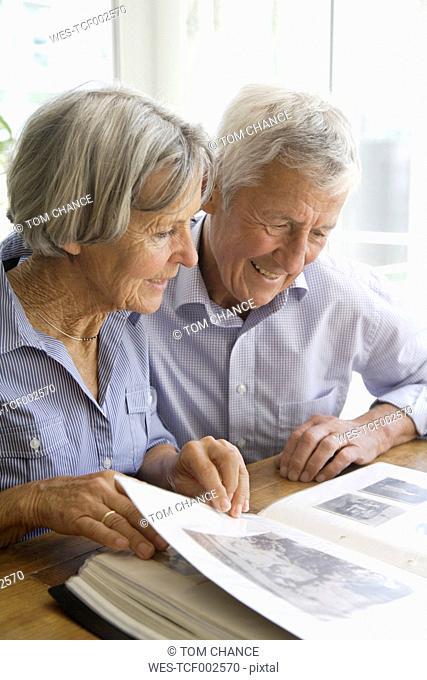 Germany, Bavaria, Senior couple with photo album, smiling