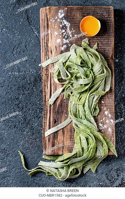 Fresh raw uncooked homemade green spinach pasta tagliatelle with egg yolk and flour on wooden chopping cutting board over dark texture concrete background