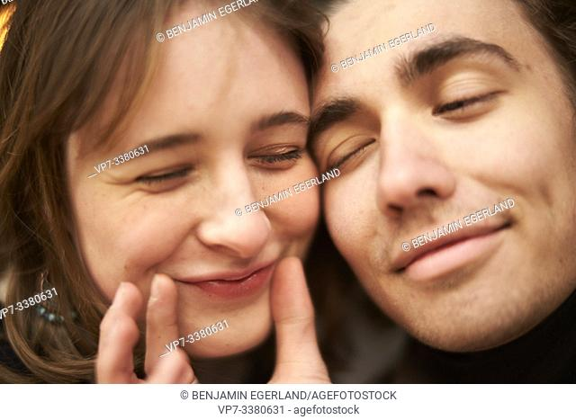 affectionate man putting a smile on face of woman