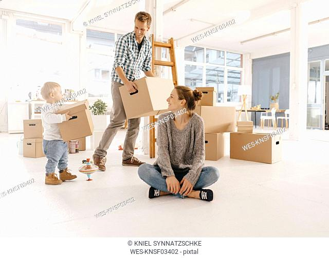 Happy family moving into new home with father and daughter carrying cardboard boxes