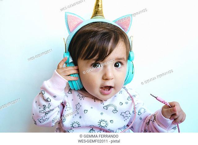 Portrait of surprised baby girl with unicorn headphones