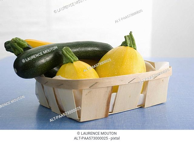 Zucchini and gold ball squash in basket