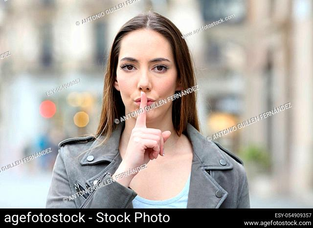 Front view portrait of serious woman asking for silence with finger on lips on city street