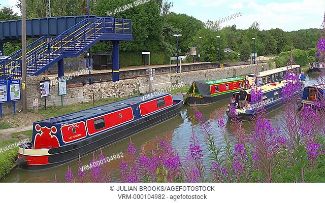 A Narrowboat passes Heyfprd railway station on the Oxford Canal