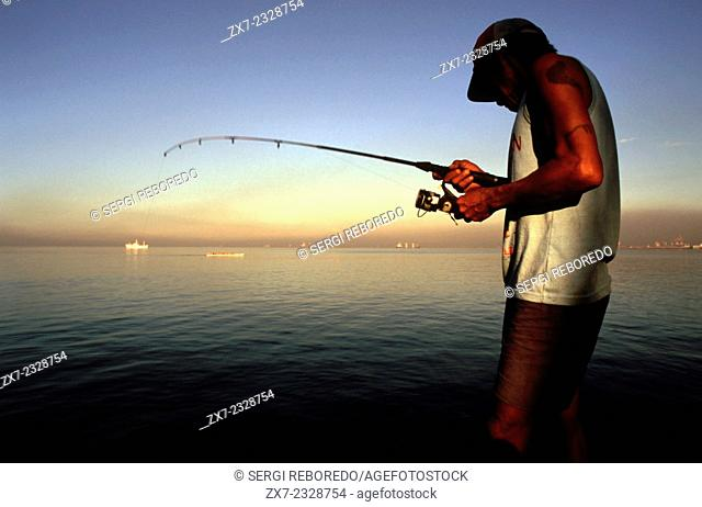 Fisherman fishing in Manila Bay. Roxas Boulevard. Manila. Philippines. Roxas Boulevard is a popular waterfront promenade in Manila in the Philippines