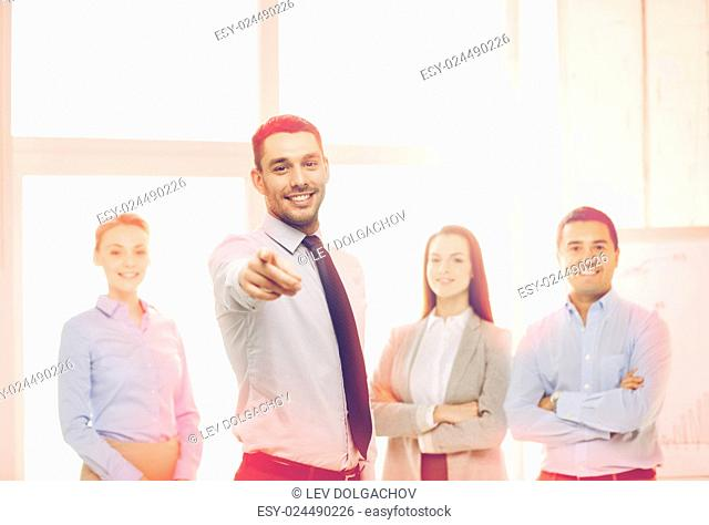 business and office concept - smiling handsome businessman with team in office pointing finger at you