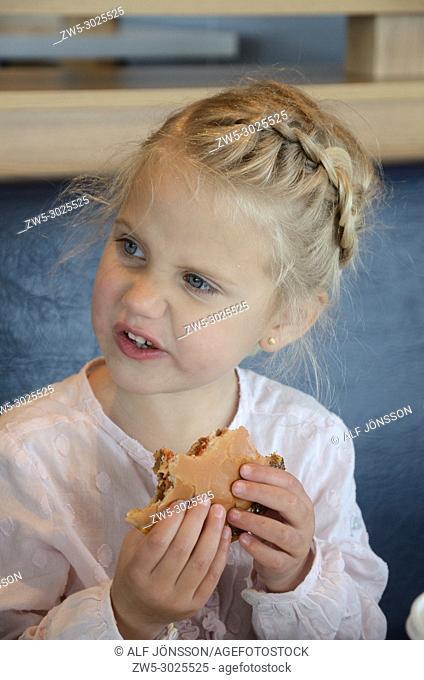 Blond eats burger in Ystad, Scania, Sweden
