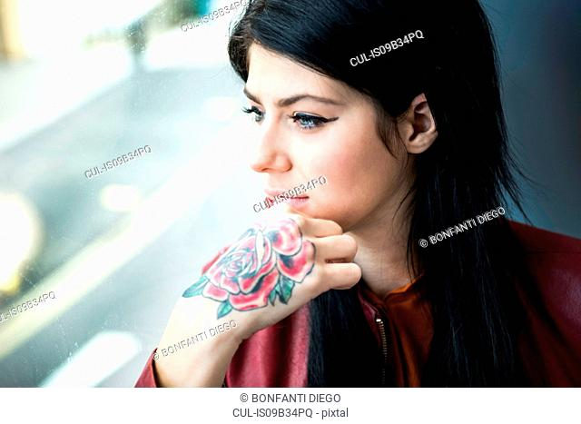 Young woman with tattoo on hand, looking through window