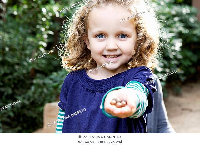 Portrait of blond little girl with a hand full of nuts
