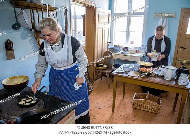 Veronika Rehhagen (l) prepares food at the historical farm kitchen of the Advent market 'Wintersonnenwerke'(lit. 'Winter Sun Works')in the open air museum...