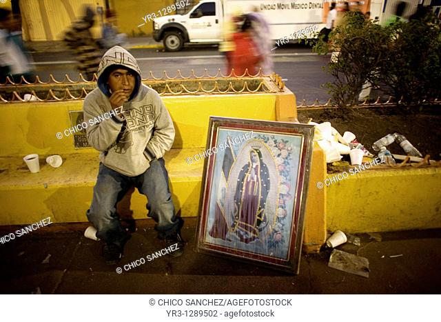 A pilgrim sits by an image of Our Lady of Guadalupe virgin in Mexico City, December 11, 2010  Hundreds of thousands of Mexican pilgrims converged on the Our...