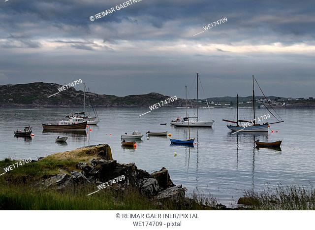 Baile Mor village harbour at dusk with moored boats and sailboats on the Sound of Iona looking from Isle of Iona to Fionnphort Isle of Mull Scotland