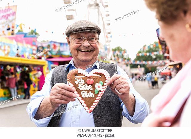 Portrait of happy senior man presenting gingerbread heart on fair