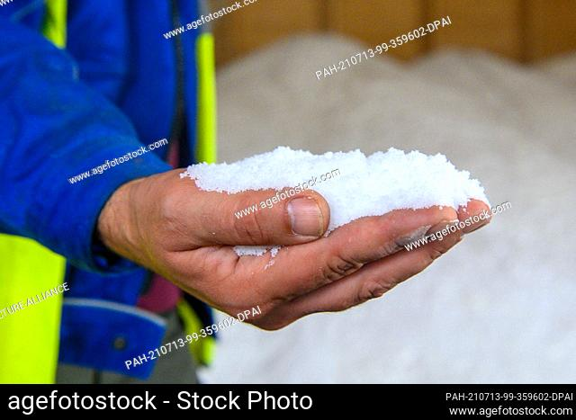 12 July 2021, Saxony-Anhalt, Staßfurt: An employee of the chemical company Ciech shows salt produced in the wet salt storage facility